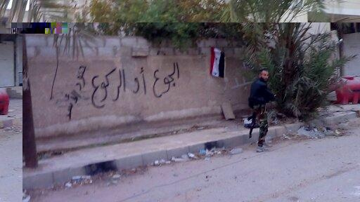"""Kneel or Starve,"" written on a wall in Moadamiya by regime soldiers"
